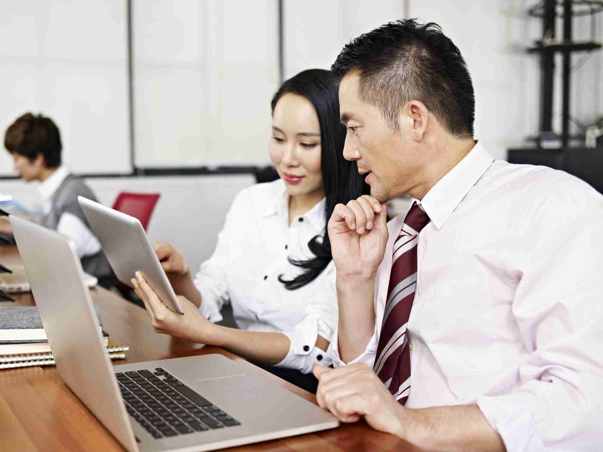 Asian-American male and female sitting next to each other with laptops looking down at a tablet . They are viewing a virtual training.