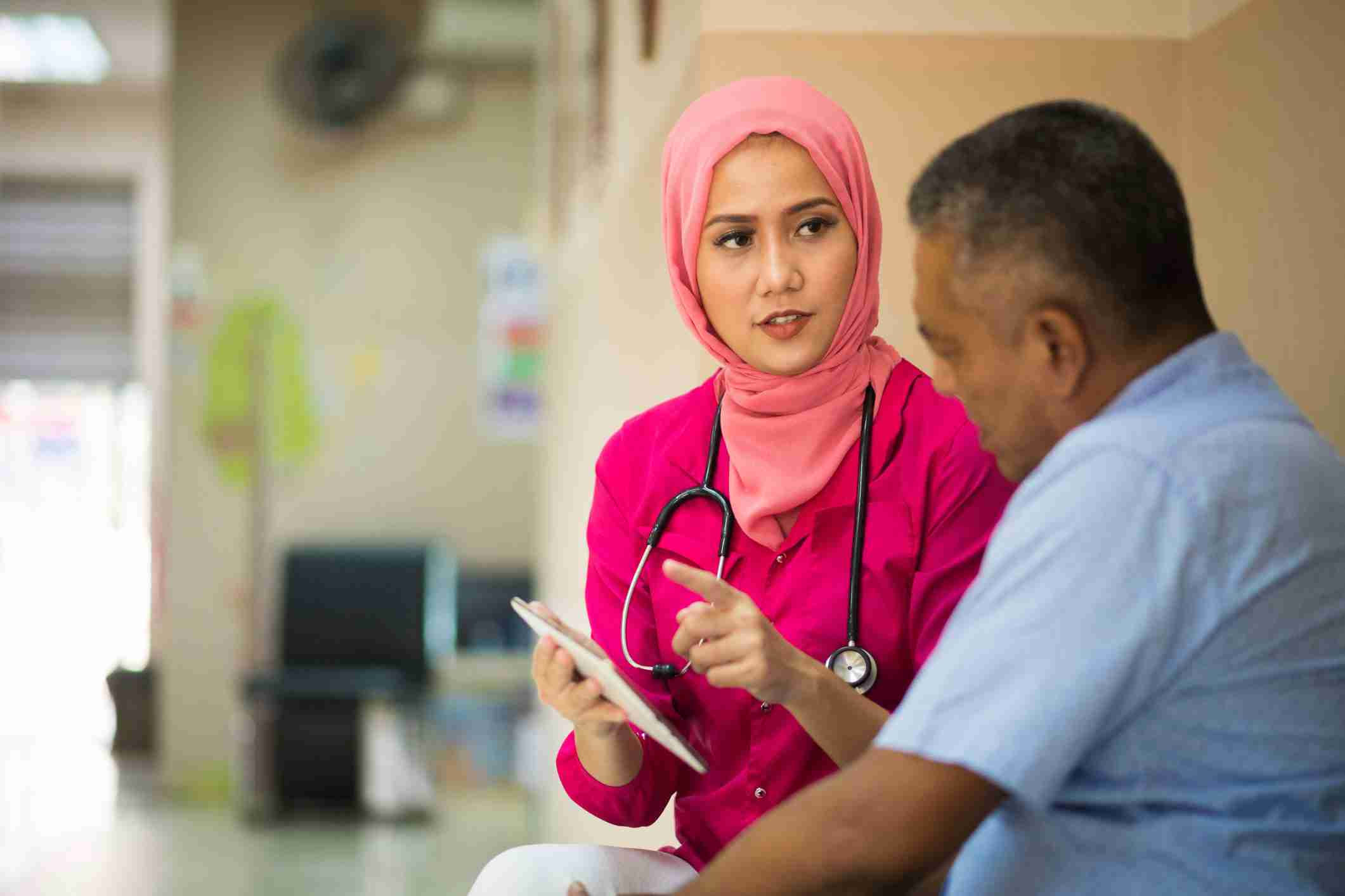 Muslim female Clinician or Registered Nurse [RN]in pink hijab, wearing a stethoscope, having a discussion with a Hispanic-American male.