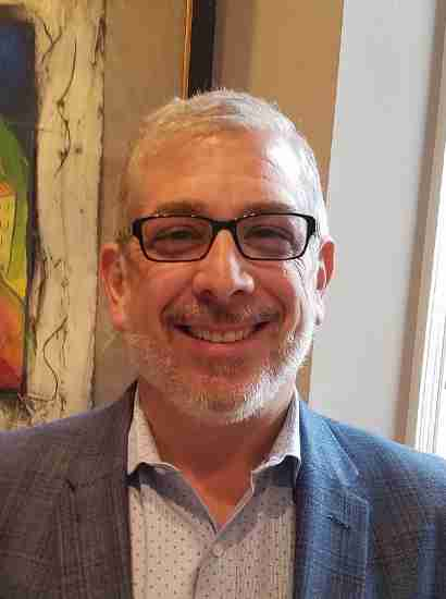 Stephen Goldberg, MD, Medical Director, Engage with Skills Training Programs, smiling, wearing glasses and grey suitcoat